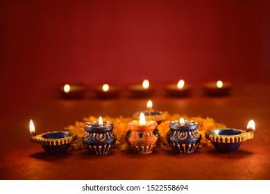 Beautiful diwali lamps with flowers on red background, Diwali Diya