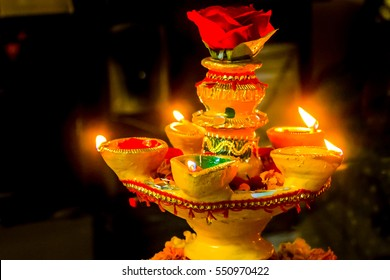 Beautiful Diya stand with litup diyas and rose decorated for Diwali or Deepawali festival celebration of Hindus across India and world