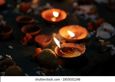 Beautiful diyas (oil lamps) are decorated on the stairs of the ghats of Varanasi, India with selective focus.  Close up shot of oil lamps during Dev Diwali festival in Benaras near river Ganges.