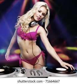Beautiful DJ girl on decks on the party wearing pink bikini