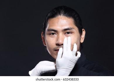 Beautiful Doctor check cheek, chin, nose, eyebrow, forehead on handsome patient man black hair tan skin before plastic surgery, studio lighting dark background