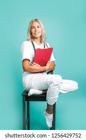 Beautiful doctor girl sitting on a chair holding a logbook