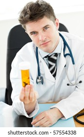 Beautiful doctor holding pills in his office