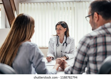 Beautiful doctor talking to a couple.