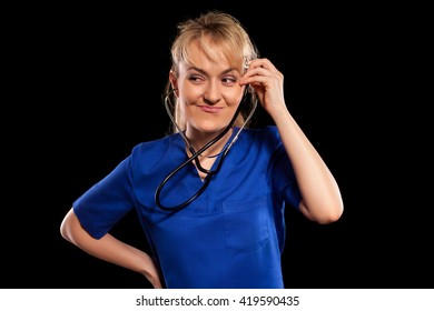 Beautiful doctor woman in blue labcoat with stethoscope showing funny gesture standing on black background