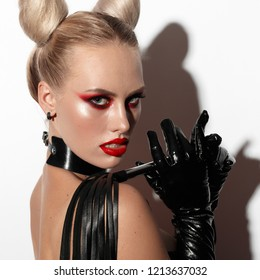 Beautiful dominant blonde devil demon vamp mistress bdsm girl with hair horns in glamour latex skirt, corset, collar and bdsm black leather fetish harness posing on white background