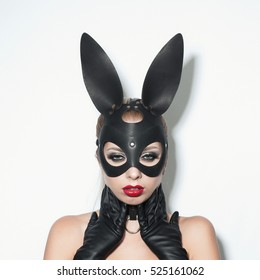 Beautiful dominant blonde vamp mistress girl in leather corset, gloves, collar and bdsm black leather fetish rabbit mask posing on white backgroung