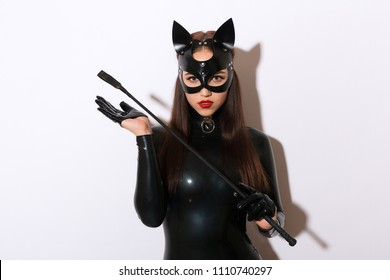 Beautiful dominant brunette vamp mistress bdsm girl with fashion makeup in glamour latex dress, collar and black leather fetish cat mask posing on white background