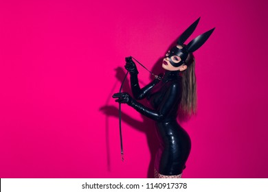 Beautiful dominant brunette vamp mistress bdsm girl with fashion makeup in glamour latex dress, collar and bdsm black leather fetish rabbit mask posing on hot pink background