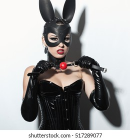 Beautiful dominant brunette vamp mistress girl in latex corset, long gloves, collar and bdsm black leather fetish rabbit mask posing with ball gag on white backgroung
