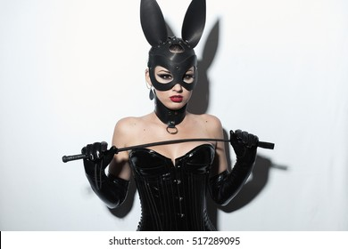 Beautiful dominant brunette vamp mistress girl in latex corset, long gloves, collar and bdsm black leather fetish rabbit mask posing with riding crop on white backgroung