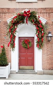 A beautiful door is decorated for Christmas with an evergreen wreath