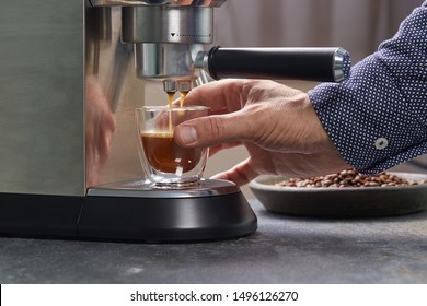 Beautiful double-circuit espresso Cup in hand is filled with coffee from home coffee machine. Household coffee makers.