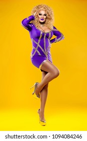 beautiful drag queen on a yellow background in a purple dress