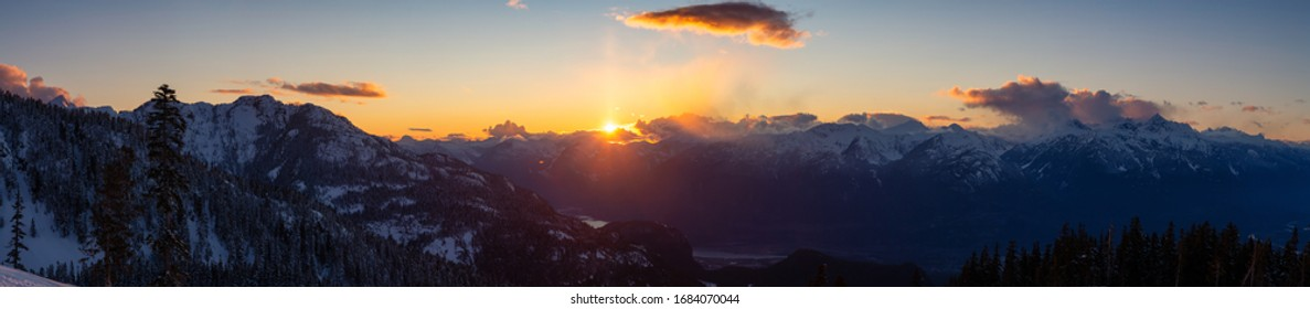 Beautiful Dramatic Canadian Mountain Landscape View during a sunny and cloudy winter sunset. Taken in Squamish, British Columbia, Canada. Nature Background Panorama