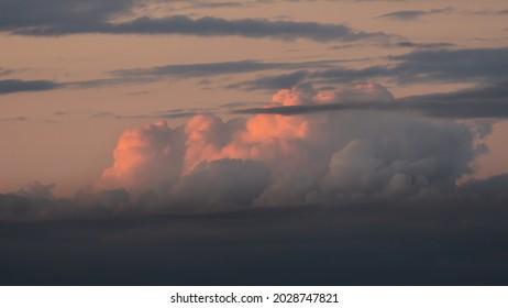 Beautiful dramatic cumulous clouds at sunset background. Orange colorful sunset dark storm clouds wallpaper