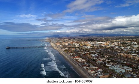 Beautiful dramatic drone panoramic aerial birds eye view Oceanside, California, Oceanside Pier Oceanside harbor and downtown plus miles of beach and dynamic cloudscape