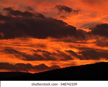 Beautiful dramatic fiery sky orange and red sunset or sunrise with dark black clouds as nature background