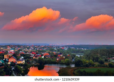 Beautiful dramatic landscape with bright pink clouds reflected in river, country houses in the light of the dawning sun and distant city in Sloboda village, Moscow region, Russia