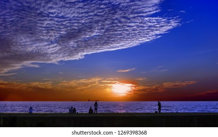 Beautiful dramatic ocean sunset and cloudscape with people watching from a pier