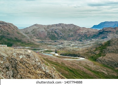 Beautiful dramatic summer landscape from northern Norway near North Cape (Nordkapp), the Finnmark area, tortuous road, scattered small lakes, rocky mountains and in the background the Barents Sea.