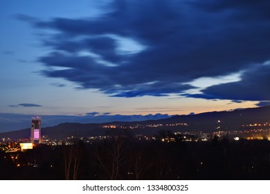 Beautiful dramatic sunset evening with fast moving clouds over town. Long exposure. Banska Bystrica, Slovakia, Central Europe.  Darkening blue sky. Day to night. City lights.