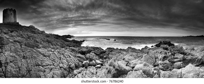 Beautiful dramatic sunset over the old Aragonese tower near Isola Rossa,Sardinia, Italy. Panorama - black and white