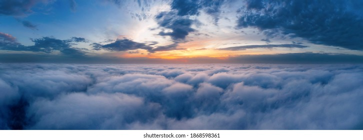 Beautiful dramatic sunset sky above fluffy clouds early in the morning from aerial drone view.