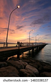 Beautiful and dramatic sunset view in UMS beach, Sabah with long concrete jetty and 3 tourists in silhouette.