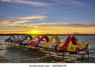 Beautiful dramatic sunset of a warm, pleasant summer day at Lake Balaton.In the foreground visible colorful pedalos.  Holiday landscape  from Hungary.