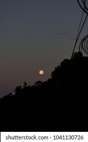 Beautiful and dramatic view of supermoon rising over a silhouette of a cable car. The image contain soft focus, noise and grain.