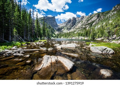 Beautiful Dream Lake in Rocky Mountains National Park, Colorado, with Hallett Peak view, green trees, deep blue sky and white clouds in the background.