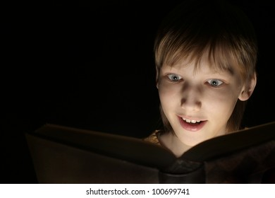 A beautiful dreamy boy with a book on a black background