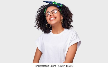Beautiful dreamy dark-skinned young woman dressed in white t-shirt, feeling happy and enjoying the weather. African American female smiling broadly, wearing round eyewear posing over white studio wall