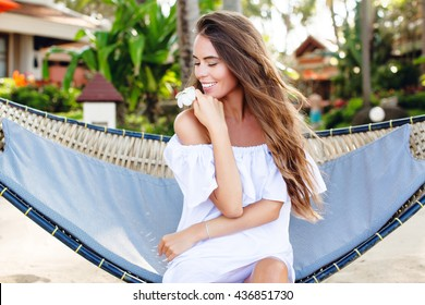 Beautiful dreamy girl sitting in a hammock on a beach with closed eyes smiling widely. She wears white dress with open shoulders and holds a flower in her hand. Girl has long dark hair.
