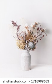 Beautiful dried flower arrangement in a stylish ceramic white vase. Dried flowers include pink proteas, banksia, gold palm leaf, kangaroo paw, cotton and ruscus leaves. - Shutterstock ID 1718999683