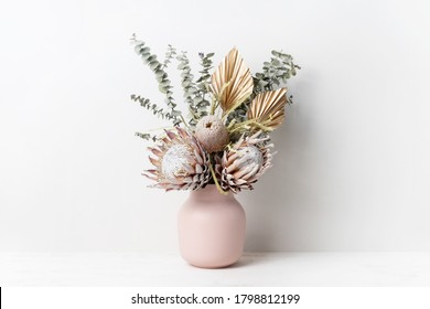 Beautiful dried flower arrangement in a stylish pink vase. In the flower bunch is pink King Proteas, Banksia, Eucalyptus leaves and golden Palm fronds, photographed on a white background. - Shutterstock ID 1798812199