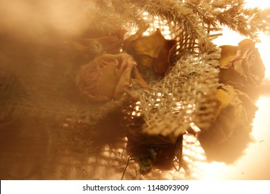 Beautiful dried roses and copper stone in pottle made of jute material with creative light effects on natural background.