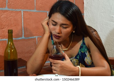 beautiful, drunken middle aged woman holding wine glass close to her lips