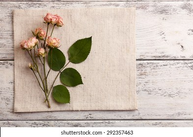 Beautiful dry flowers on napkin on wooden background