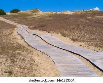 Beautiful Dune at Curonian Spit near Nida, Neringa, Lithuania, awesome nature summer landscape with wooden path. lot of sand, blue sky, plants and Baltic Sea