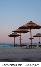 Beautiful dusk and blue hour light just after sunset in a beach club in Villasimius, Sardinia, italy. Straw sub umbrellas and wooden sunbeds, soft pink sky, summer magic atmoshpere.