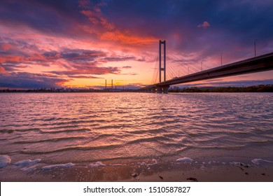 Beautiful dusk landscape with bridge over river Dnipro. Dramatic colorful sky.
