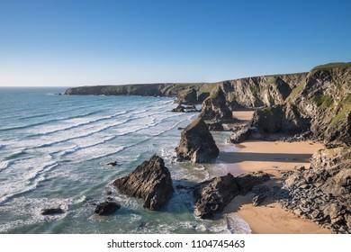 Beautiful dusk sunset landscape image of Bedruthan Steps rock stacks on West Cornwall coast in England