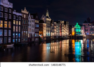 Beautiful Dutch houses by the canal during the late evening water reflection in Amsterdam Capital city