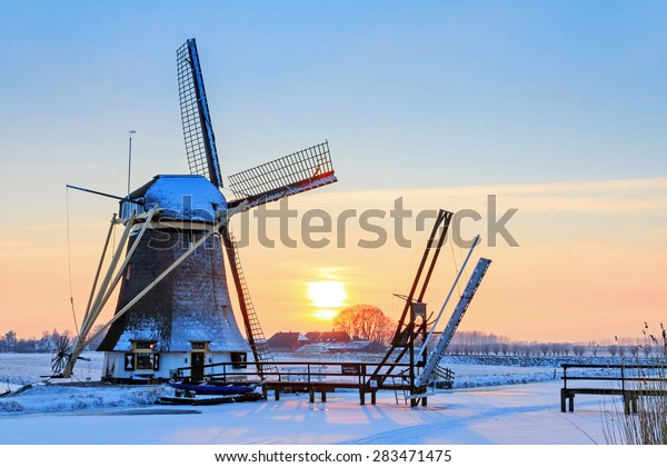 Beautiful dutch windmill near Baambrugge in the Netherlands, covered in snow with ice on the river at sunset