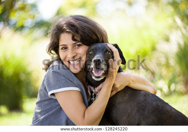 Beautiful early 40s woman hugging her black labrador retriever dog at a park