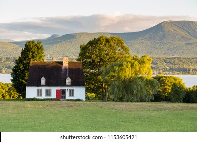 Beautiful early morning summer view of patrimonial white wooden house with steep shingled roof in rural setting with trees, river and mountains in the background, Island of Orleans, Quebec, Canada
