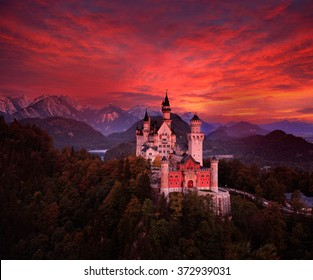 Beautiful early morning view of the Neuschwanstein fairy tale castle, bloody dark sky with autumn colors on the sky during sunrise, twilight on Bavarian Alps, Bavaria, Germany.