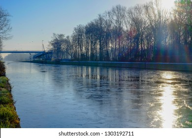 Beautiful early winter landscape with a frozen river or canal, treelined riverside and grass at sunrise creating a tranquile and quiet scenic nature background
